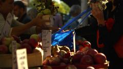 Women buy apples and flowers at Farmer's Market Stock Footage