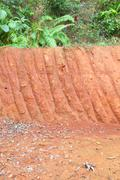 vertical red cliff of small level ground dig a well. - stock photo