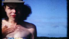 549 - woman rubs sun tan oil on upper chest - vintage film home movie Stock Footage