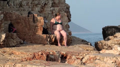 Fat woman on rock at the seaside zoom out Stock Footage