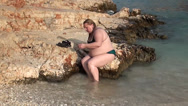 Stock Video Footage of A fatty after swim sitting on rock