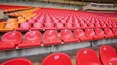 Rows of red and orange plastic seats at stadium tribune Stock Footage