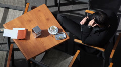 Man speaks by cell phone during sit at cafe tables on street Stock Footage