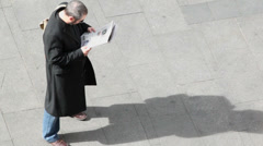 Man reads paper on pavement at sunny day Stock Footage
