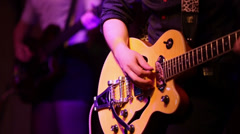 Young man and woman play on guitars on stage during concert Stock Footage