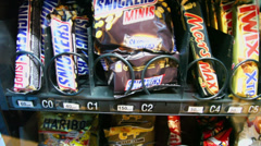 Bar of chocolate falls down from showcase of machine in airport Stock Footage