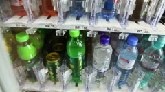 Bottle of water moves from showcase of machine in airport Stock Footage