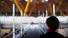 Woman walks by passage at second level of Madrid Barajas Airport Stock Footage