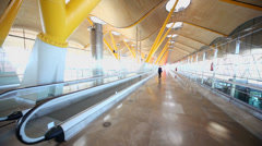 Woman walks by empty hallway in Madrid Barajas Airport Stock Footage