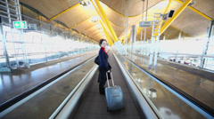 Woman rides with luggage by empty hallway in Barajas Airport Stock Footage