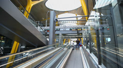 Travelers ride by escalator in Madrid Barajas Airport Stock Footage