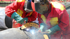 Workers welding pipe, teamwork Stock Footage