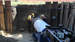 Workers welding large pipe in a hole, teamwork - stock footage