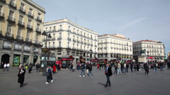 People walk at Puerta del Sol near monument to Carlos III - stock footage