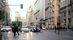 Pedestrians cross Gran Via street with cars Stock Footage