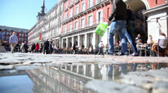 Tourists walk and sit at tables in cafe at Plaza Mayor Stock Footage