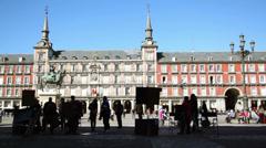 People walk near street painters workplace at Plaza Mayor Stock Footage