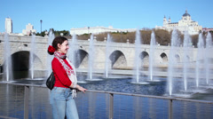 Happy young woman stands and smiles near bridge - stock footage