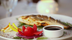 Grilled fish circling on dish with tomato, herbs, onions Stock Footage
