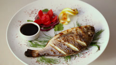 Grilled fish spins on dish with tomato, herbs, onions Stock Footage