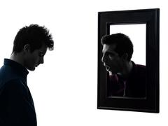 Man in front of his mirror silhouette Stock Photos