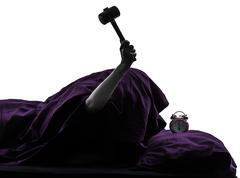 one person bed smashing alarm clock silhouette - stock photo