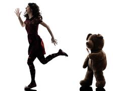 Strange young woman and killer teddy bear silhouette Stock Photos