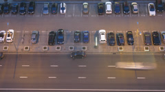 Aerial view of car traffic on street at night and parking lot Stock Footage