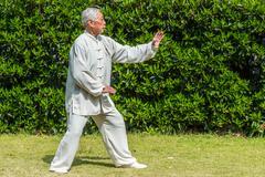 Yksi vanha mies käyttäessään kung fu Fuxing puistossa Shanghaissa Kiinassa Kuvituskuvat
