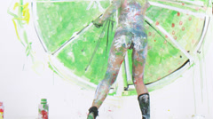 Woman covered in painting drawing on the wall, timelapse Stock Footage