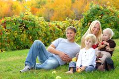 happy family sitting in the grass eating apples at orchard - stock photo