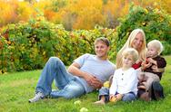 Stock Photo of happy family sitting in the grass eating apples at orchard