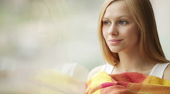Cute young woman looking out of window wrapping herself with warm plaid blank Stock Footage