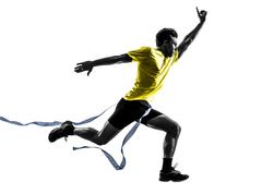 Young man sprinter runner running winner finish line silhouette Stock Photos