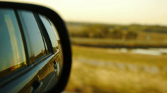 Rearview side car mirror while driving by lake and highway rack focus Stock Footage
