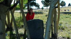 Woman visiting grave in small town cemetary on a fall day Stock Footage