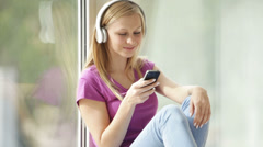 Beautiful girl in headphones sitting by window using cellphone looking at camera - stock footage