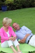 Senior couple relaxing on a rug on the grass Stock Photos