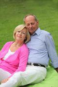 Loving senior couple relaxing outdoors Stock Photos