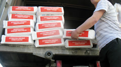 Three workers unloading a truck of plaster bags Stock Footage