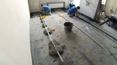Three workers preparing the floor to put cement, timelapse Stock Footage
