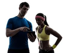 Woman exercising fitness  man coach using digital tablet Stock Photos