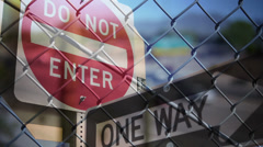 Traffic Signs, Chain Link Fence, and Traffic Overlay - stock footage