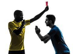 Two men soccer player and referee showing red card silhouette Stock Photos