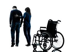 Man with woman  walking away from  wheelchair  silhouette Stock Photos