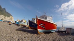 Fishing boats on the shingle beach at Beer in Devon England - stock footage