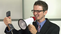 Manager screaming with megaphone at telephone Stock Footage