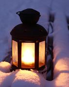 Candle lamp on snowy bench Stock Photos