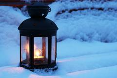 Stock Photo of candle lamp on snowy bench