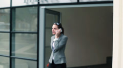 Businesswoman talking on cellphone and walking out of office building HD Stock Footage